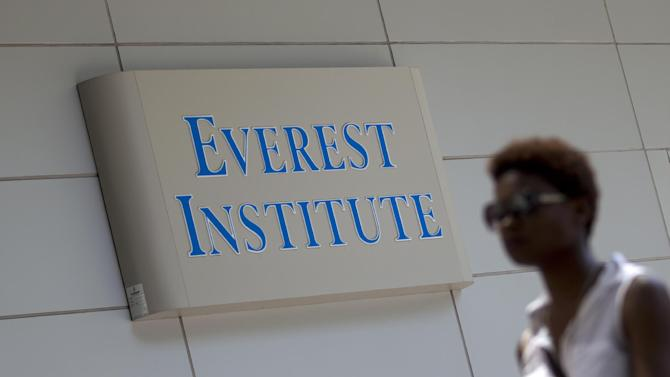 "FILE - In this July 8, 2014 file photo, a woman walks past the Everest Institute in Silver Spring, Md. Corinthian Colleges, which owns Everest, Heald College and WyoTech schools, is being sued by the federal Consumer Financial Protection Bureau for what it calls a ""predatory lending scheme,"" the agency said Tuesday, Sept. 16, 2014. (AP Photo/Jose Luis Magana, File)"