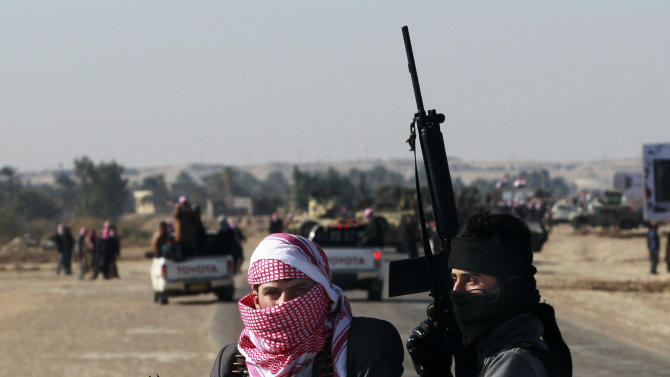 Sahwa members, a group of Sunni Arabs who joined forces with the U.S. military to fight al-Qaida at the height of Iraq's insurgency, escort the coffin of Ifan Saadoun al-Issawi, during his funeral in Fallujah, 40 miles (65 kilometers) west of Baghdad, Iraq, Wednesday, Jan. 16, 2013. The Sunni-backed Iraqiya bloc lawmaker was killed by a suicide bomber in Fallujah on Tuesday. (AP Photo/ Hadi Mizban)