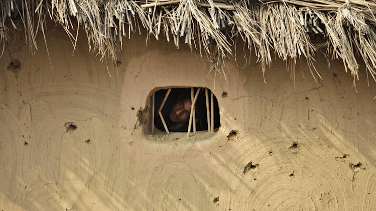 A villager looks out a window of a hut damaged allegedly by gunfire from the Pakistan side of the border at Jora Farm village, in Ranbir Singh Pura region, about 35 kilometers (22 miles) from Jammu, India, Saturday, Aug. 23, 2014. India and Pakistan traded gunfire in the disputed Kashmir region on Saturday, killing two villagers on each side and wounding several others, officials said. Tensions have escalated in Kashmir since India earlier in the week called off diplomatic talks with Pakistan because the Pakistani ambassador in New Delhi met with separatist leaders from the disputed region. (AP Photo/Channi Anand)