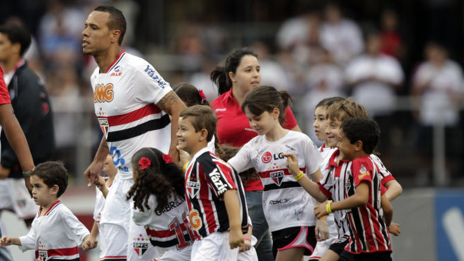 Accompanied by children, Sao Paulo FC's Luis Fabiano, top, enters the field before a Brazilian soccer league match against Flamengo in Sao Paulo, Brazil, Sunday, Oct. 2, 2011. (AP Photo/Andre Penner)