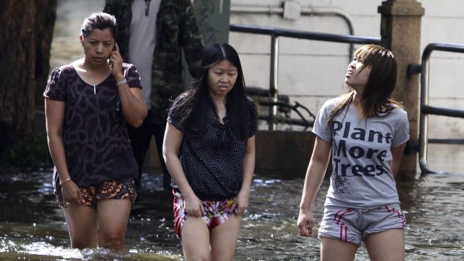 Thai women negotiate a flooded area in Bangkok, Thailand, Saturday Oct. 29, 2011. The complex network of flood defenses erected to shield Thailand's capital from the country's worst floods in nearly 60 years was put to the test Saturday as coastal high tides hit their peak. (AP Photo/Aaron Favila)