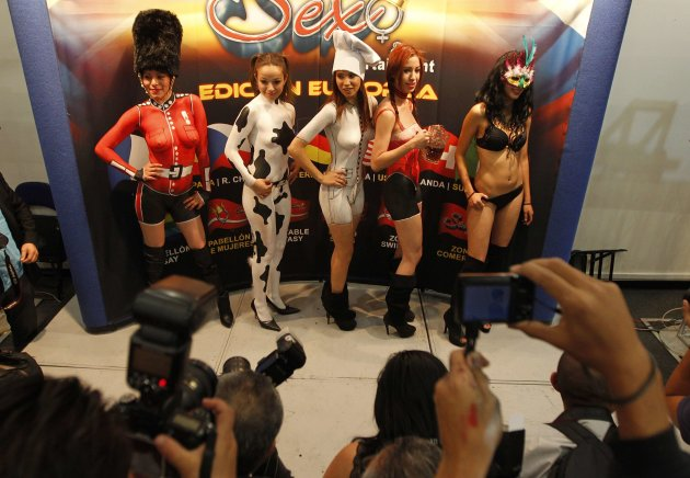 Dancers in body paint pose for pictures during a news conference to promote the