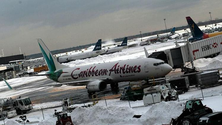 A Caribbean Airlines flight sits near machinery moving snow at Terminal 4 of John F. Kennedy International Airport December 28, 2010 in New York City