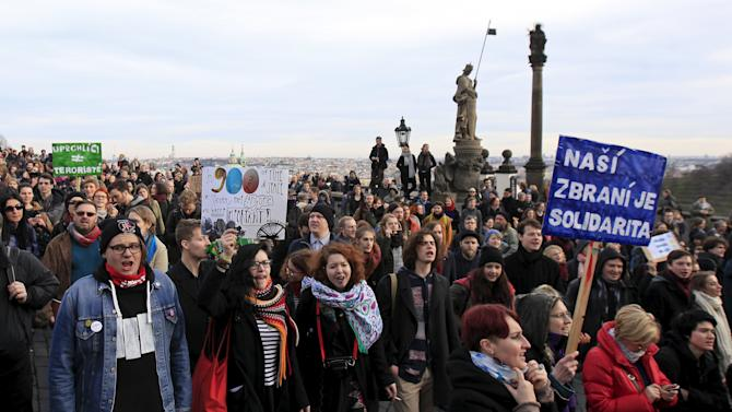 Protestors hold banners  and shout slogans during a pro-immigration rally in support of refugees in Prague