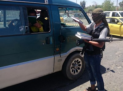 A fighter with the al-Qaida-inspired Islamic State of Iraq and the Levant (ISIL) distributes a copy of the Quran, Islam's holy book, to a driver in ce...