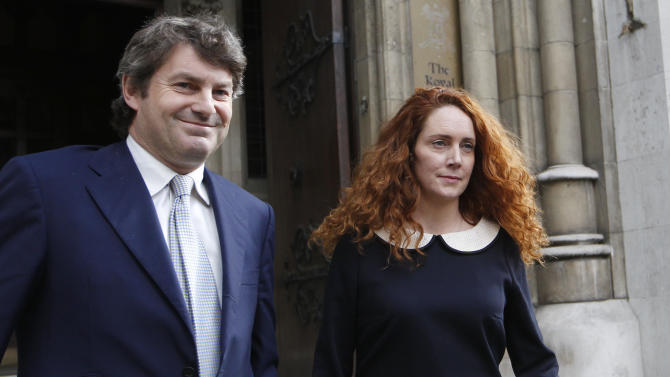Rebekah Brooks, former chief executive of News International and her husband Charlie Brooks leave the High Court in London after giving evidence to the Leveson Inquiry, Friday, May 11, 2012. The Leveson Inquiry is Britain's media ethics probe that was set up in the wake of the scandal over phone hacking at Rupert Murdoch's News of the World, which was shut in July 2011 after it became clear that the tabloid had systematically broken the law. (AP Photo/Sang Tan)