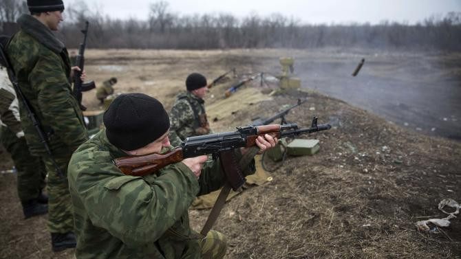 Volunteers of the separatist self-proclaimed Donetsk People's Republican guard fire their weapons during shooting training in Donetsk