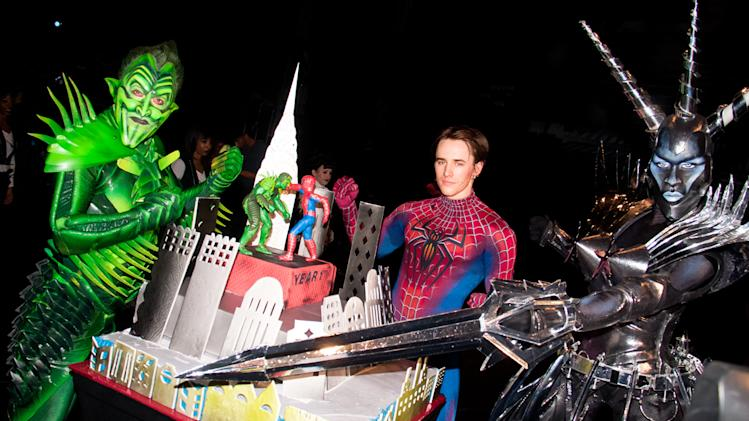 """In this Nov. 27, 2011 photo released by The O and M Co., from left, Patrick Page, dressed as Green Goblin, Reeve Carney, dressed as Spider-Man and Sean Samuels, as Swiss Miss pose with an elaborate cake celebrating the first anniversary of the Broadway musical, """"Spider-Man: Turn Off the Dark,"""" in New York. (AP Photo/The O and M Co., Peter James Zielinski)"""