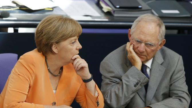 German Chancellor Merkel speaks with Finance Minister Schaeuble during a parliamentary debate on the Greek debt crisis at the German lower house of parliament Bundestag in Berlin