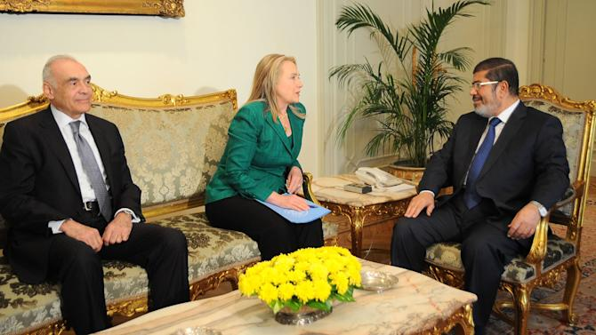 "In this photo released by the Egyptian Presidency, U.S. Secretary of State Hillary Rodham Clinton, center, meets with Egyptian President Mohammed Morsi, right, and Egyptian Foreign Minister Mohammed Kamel Amr, left, in Cairo, Egypt, Wednesday, Nov. 21, 2012. Secretary of State Hillary Rodham Clinton has arrived in Cairo in her diplomatic push to forge a truce between Israel and Gaza rulers of Hamas. Her visit comes hours after a bomb exploded on an Israeli bus in Tel Aviv, wounding several. Clinton is looking to piece together a deal to end Israel's weeklong offensive in the Gaza Strip. Clinton said the U.S. ""strongly condemns"" today's bus bombing, calling it a ""terrorist attack."" (AP Photo/Egyptian Presidency)"