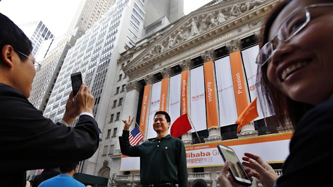 FILE - In this Friday, Sept. 19, 2014 file photo, Arthur Jiang, of Beijing,  poses for a photograph in front of the New York Stock Exchange on the day of Alibaba's initial public offering in New York. Growing confidence was also evident in the number of companies looking to float their shares on the stock market. One of the biggest of all-time was Alibaba, the Chinese e-commerce company, which raised around $25 billion. (AP Photo/Jason DeCrow, File)