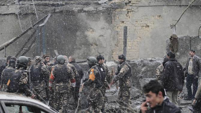 Security men with the Afghan intelligence service are seen at the scene of a suicide car bomb attack in Kabul, Afghanistan, Wednesday, Jan. 16, 2013. Six militants — one driving a car packed with explosives — attacked the gate of the Afghan intelligence service in the capital Kabul on Wednesday, setting off a blast that could be heard throughout downtown and which sent a plume of dark smoke rising into the sky. (AP Photo/Ahmad Jamshid)