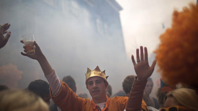 People dance inhe street in Amsterdam, The Netherlands, Tuesday April 30, 2013. Around a million people are expected to descend on the Dutch capital for a huge street party to celebrate the first new Dutch monarch in 33 years.  (AP Photo/Emilio Morenatti)