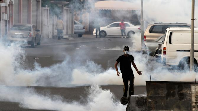 Bahraini anti-government protesters clash with plain clothes police firing tear gas during clashes in Sanabis, Bahrain, Monday, Feb. 11, 2013. After nearly two years of nonstop unrest, opposing factions in Bahrain began talks on Sunday to ease an Arab Spring conflict that has run longer than Syria's rebellion and is playing out on the doorstep of the U.S. military's main naval base in the Persian Gulf. (AP Photo/Hasan Jamali)