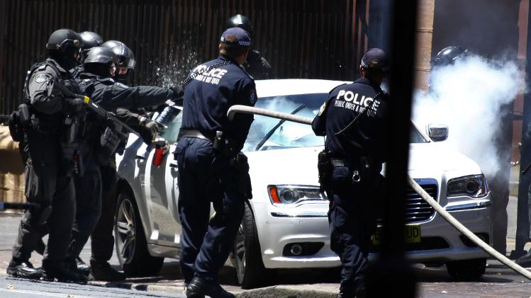 Heavily armed police officers prepare to drag a man from his car outside the New South Wales state parliament building in Sydney