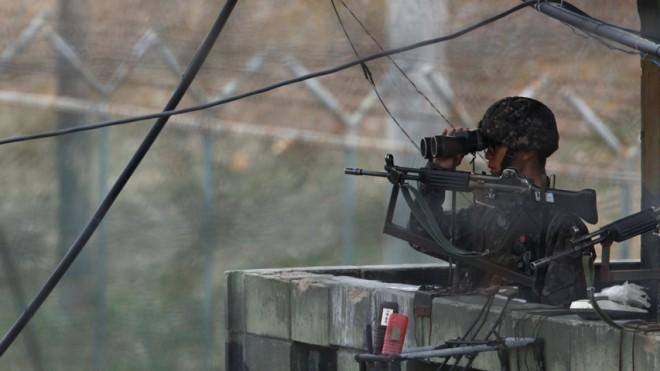 A South Korean soldier looks to the north through a pair of binoculars at an observation post near the demilitarized zone north of Seoul on April 5.
