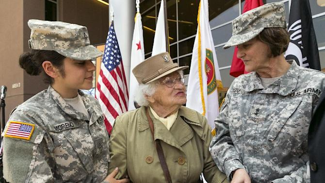 United States Army Maj. Gen. Megan Tatu, right, holds hands with Bea Cohen, 103, center, the oldest female World War II Army veteran in Calif., and Pfc. Ana Moreno, 24, left, the youngest soldier present at the ceremony join U.S. Army veterans celebrating the Army's 238th birthday, Flag Day at the third anniversary of the West Los Angeles Veterans Home in Los Angeles, Friday, June 14, 2013. (AP Photo/Damian Dovarganes)