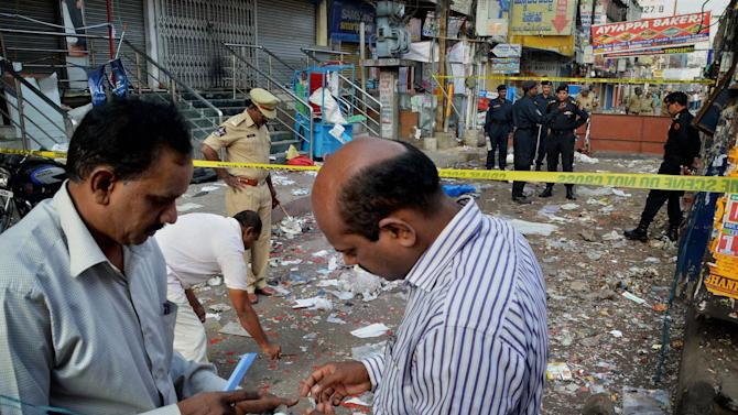 Officials of India's National Investigation Agency collect evidence in the debris at one of the two bomb blast sites, in Hyderabad, India, Friday, Feb. 22, 2013. A day after two bicycle bombs killed more than a dozen people and wounded more than 100, investigators into India's worst bombing in more than a year searched Friday for possible links to anger over the execution of a Muslim militant. (AP Photo)