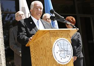 Torrance Mayor Frank Scotto, at podium, holds a news …