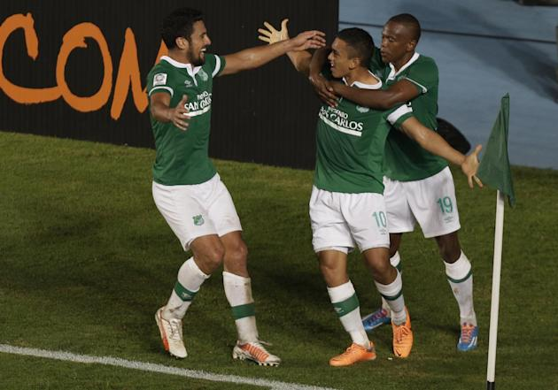 Carlos Lizarazo, center, of Colombia's Deportivo Cali celebrates with teammates Andres Perez, left, and Yerson Candelo, right, after scoring from a penalty kick against Argentina's Lanus durin
