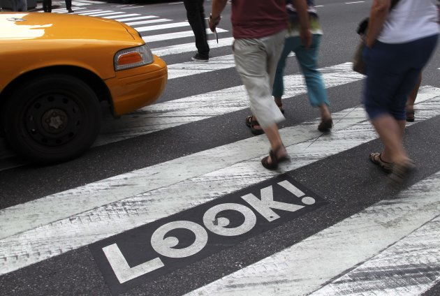 "Pedestrians walk past a ""Look!"" sign on the crosswalk at the intersection of 42nd St. and 2nd Ave. in New York, Thursday, Sept. 20, 2012. Crossing the street in New York City is complicated: Even when it's one-way, you should look both ways, and stop texting for a few seconds. That's what city transportation officials tell pedestrians who often miss getting hit in the chaotic every-which-way-including-loose mill of vehicles, bicycles, scooters and sometimes, carriage horses. They're making their point visible with ""LOOK!"" signs stenciled at 110 of the most dangerous intersections in the city's five boroughs. (AP Photo/Seth Wenig)"