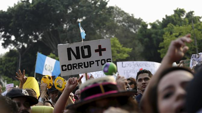 "Protesters shouts slogans and hold a sign which reads as ""No more corrupt"", during a demonstration against a political corruption scandal, in downtown Guatemala City"