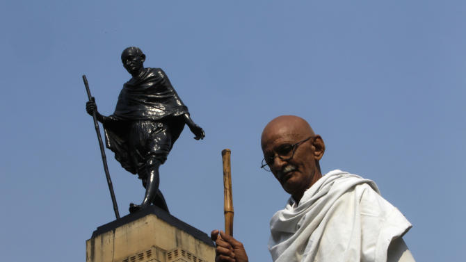 Mahesh Chaturvedi, who dresses up like Mahatma Gandhi, poses for a photo in front of a Gandhi statue in New Delhi