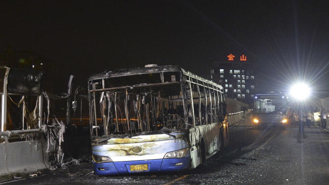 In this photo taken Saturday, June 8, 2013, charred remains of an express bus that caught fire on June 7, killing 47 people, sits on an elevated highway in Xiamen, southeast China's Fujian province. The official version of the last week's fire that gutted the bus in a prosperous port city in southeast China and left bodies piled up inside has been greeted with a derision by suspicious netizens that shows deep-seated distrust between Chinese and their government. (AP Photo) CHINA OUT