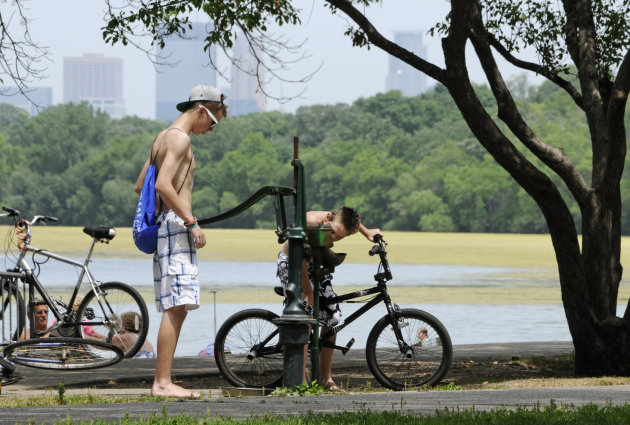 The skyline rises through haze as one boy pumps water for another to drink from an old-fashioned water pump along Lake Harriet Friday, July 6, 2012 in Minneapolis where temperatures reached into the u