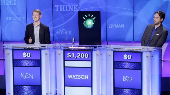 """FILE - In this Jan. 13, 2011, file photo, """"Jeopardy!"""" champions Ken Jennings, left, and Brad Rutter, right, flank a prop representing Watson during a practice round of the """"Jeopardy!"""" quiz show in Yorktown Heights, N.Y. Watson, the question-answering supercomputer is going to college. IBM is announcing Wednesday that it will provide a Watson system to Rensselaer Polytechnic Institute, the first time a version of the computer is being sent to a university. (AP Photo/Seth Wenig, File)"""