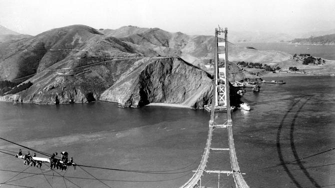 File - In an Oct. 25, 1935 file photo, workers complete the catwalks for the Golden Gate Bridge, prior to spinning the bridge cables during construction in San Francisco. The bridge was heralded as an engineering marvel when it opened in 1937. It was the world's longest suspension span and had been built across a strait that critics said was too treacherous to be bridged. As the iconic span approaches its 75th anniversary, the engineers who have overseen it all these years say keeping it up and open has been a feat unto itself.(AP Photo, File)