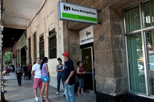 <p>Cubans make a line to enter the Metropolitan Bank, on November 24, 2011, in Havana. Cuba's state-run banks on Thursday were given permission to issue loans based on hard collateral, more than a half-century after pawnshops were banned on the communist-run island.</p>