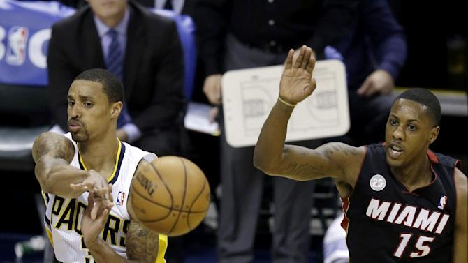 Indiana Pacers' George Hill makes a pass against Miami Heat's Mario Chalmers (15) during the first half of Game 3 of the NBA Eastern Conference basketball finals in Indianapolis, Sunday, May 26, 2013. (AP Photo/Michael Conroy)