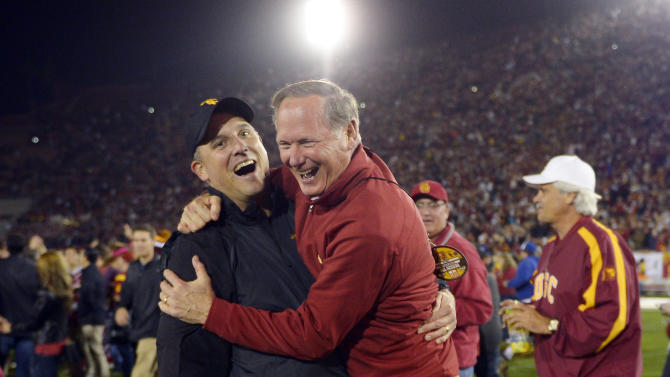 FILE - In this Nov. 16, 2013 file photo, Southern California athletic director Pat Haden, right, jumps into the arms of offensive coordinator Clay Helton after USC defeated Stanford in an NCAA college football game in Los Angeles. Helton will assume the USC helm as interim coach after Haden fired Steve Sarkisian Monday, Oct. 12, 2015. Helton was named interim coach Sunday, one day after Sarkisian was put on leave.(AP Photo/Mark J. Terrill, File)