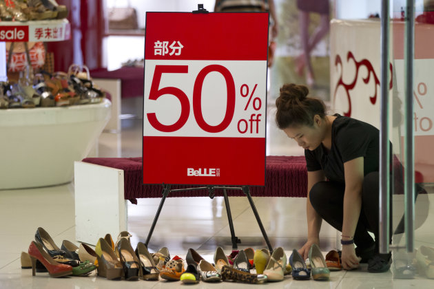 A shoe shop worker arranges discounted shoes at a shopping mall in central Beijing, China, Thursday, Aug. 9, 2012. China's inflation rate fell further in July, giving the government more room to stimulate growth amid mixed signals about whether the world's second-largest economy is recovering from a painful slowdown. (AP Photo/Alexander F. Yuan)