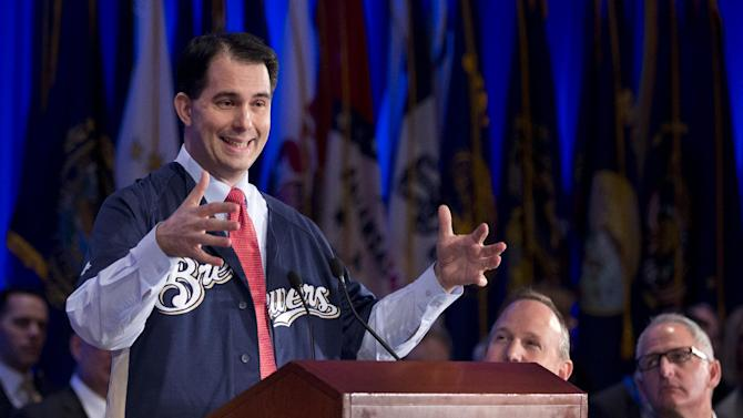 Wisconsin Gov. Scott Walker, left, sporting his state's Major League Baseball team the Milwaukee Brewers' team jersey, sends his invitation to the delegates of the National Governors Association 2013 Winter Meeting in Washington, Saturday, Feb. 23, 2013, inviting them for the next NGA meeting to the host state and to watch the Brewers' game. Seated, from center to right, are NGA Chairman Gov. Jack Markell of Delaware and Walgreens CEO and President Gregory Wasson.  (AP Photo/Manuel Balce Ceneta)