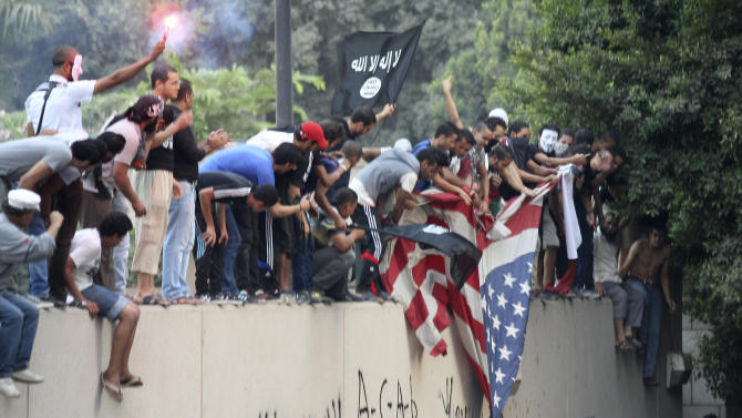 FILE - In this Sept. 11, 2012 file photo, protesters destroy an American flag pulled down from the U.S. embassy in Cairo, Egypt, during a protest of a film deemed offensive of Islam. 2012 was a year of storms, of raging winds and rising waters, but also broader turbulence that strained our moorings. And old enmities and grievances resurfaced in the Middle East, clouding the legacy of the 2011 Arab spring. (AP Photo/Mohammed Abu Zaid, File)
