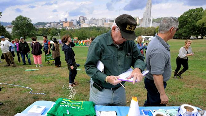 A man signs a petition during a global Frackdown Day calling for a moratorium on Shale Gas Drilling at Schenley Park in Pittsburgh, Saturday, Sept. 22, 2012.  (AP Photo/John Heller)