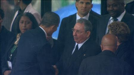 U.S. President Obama shakes hands with Cuban President Castro during Nelson Mandela's national memorial service in Johannesburg