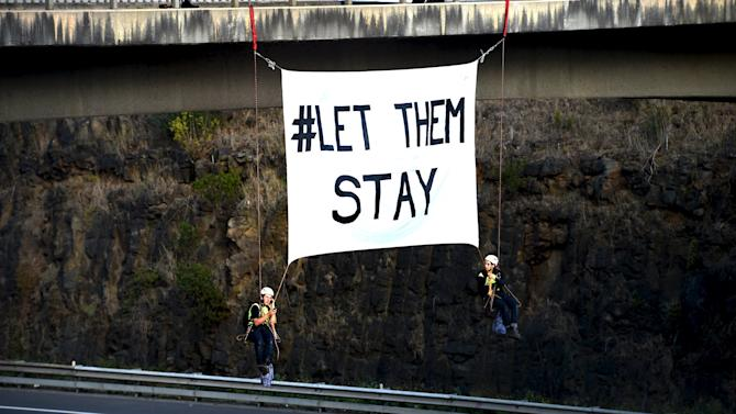 Protesters against the Nauru detention centre hang from a bridge above a freeway in Melbourne