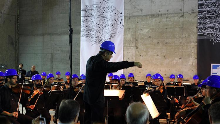 Musicians of Thessaloniki's State Symphony Orchestra peform during a concert at a metro station construction site in the northern Greek city of Thessaloniki, Friday, Aug. 29, 2014. (AP Photo/Nikolas Giakoumidis)