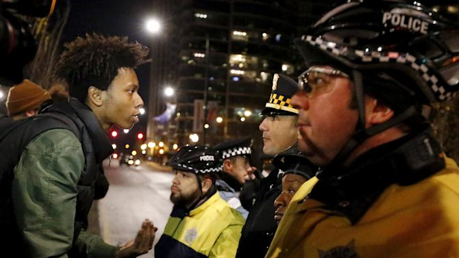 A demonstrator confronts police officers during protests in Chicago, Illinois