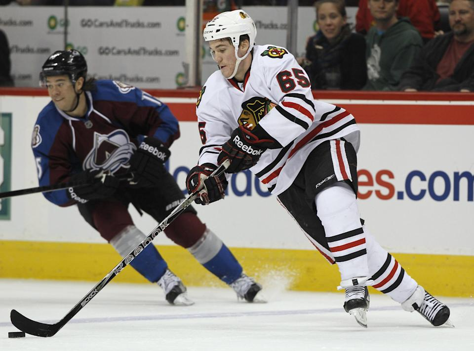 Chicago Blackhawks right wing Andrew Shaw, front, picks up a loose puck as Colorado Avalanche right wing PA Parenteau skates nearby during the third period of the Avalanche's 6-2 victory in an NHL hockey game in Denver on Friday, March 8, 2013. (AP Photo/David Zalubowski)