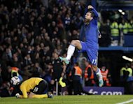Chelsea's Belgian midfielder Eden Hazard celebrates scoring his late penalty to take the game to extra time as Manchester United's Danish goalkeeper Anders Lindegaard reacts during the English League Cup Fourth Round football match between Chelsea and Manchester United at Stamford Bridge in London. Chelsea won 5-4 in extra time