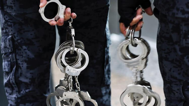 Immigration officers carry pairs of handcuffs at Kuala Lumpur International Airport