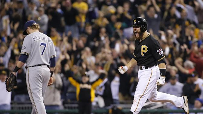 Pittsburgh Pirates' Russell Martin (55) rounds first base past Milwaukee Brewers first baseman Mark Reynolds (7) after hitting a three-run home run off Milwaukee Brewers relief pitcher Jonathan Broxton during the eighth inning of a baseball game in Pittsburgh Friday, Sept. 19, 2014. The Pirates won 4-2. (AP Photo/Gene Puskar)