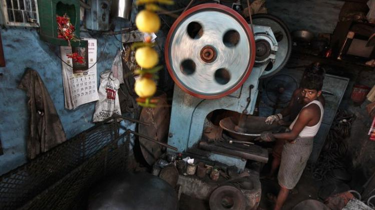 A worker moulds iron plates on a lathe to make giant utensils, at an iron utensils manufacturing unit in Kolkata