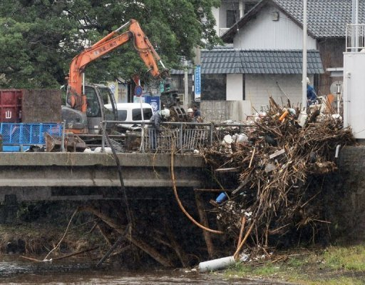Workers remove debris from the railing of a bridge in Kumamoto prefecture, on Japan's southern island of Kyushu, on July 13. Evacuation orders had been issued to about 240,000 people in the north of Kyushu where more rivers burst their banks, public broadcaster NHK and Jiji Press news agency reported, compiling figures from various authorities
