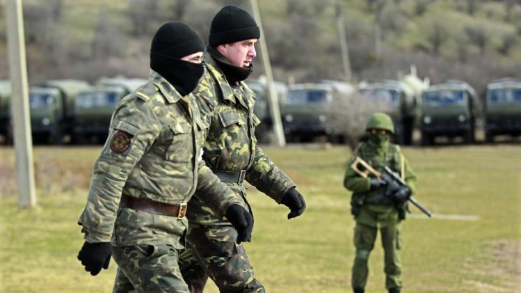 Ukrainian servicemen walk past an armed man, believed to be Russian, at the Ukrainian military base in Perevalnoye, outside Simferopol