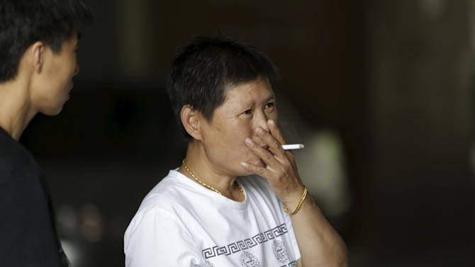 A woman smokes a cigarette outside an office building in Beijing